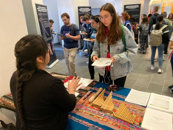 Photograph of student and faculty member discussing exhibit of artifacts