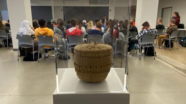 Photograph of Potawatami basket display and audience listening to Professor Daniel Rivers