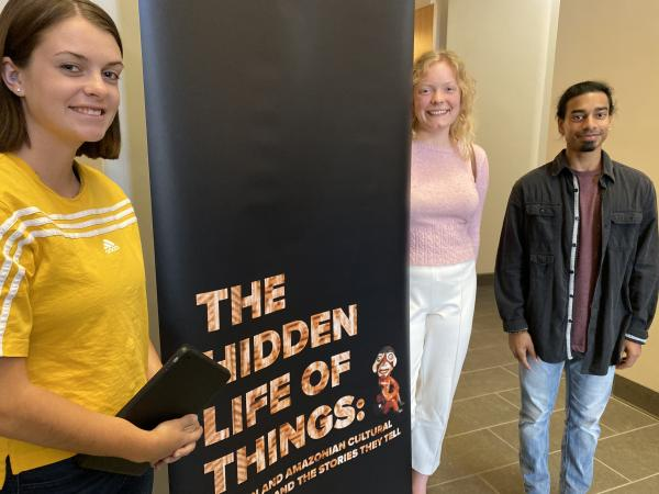 "Photograph of student curators along the title banner of ""The Hidden Life of Things"" exhibit"