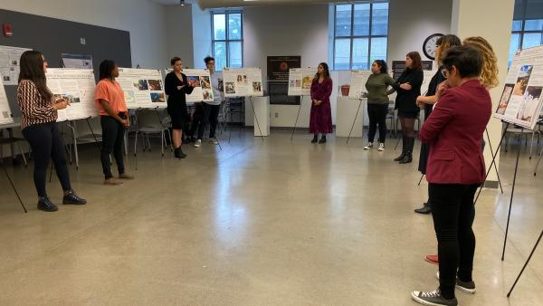 Photograph of graduate students standing in a half circle by their research posters