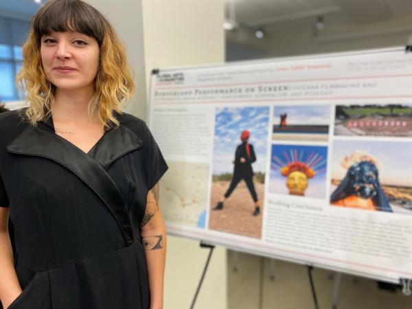 Photograph of graduate student in front of their research poster
