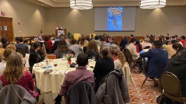 Photograph of Becca Heller speaking to crowded ballroom
