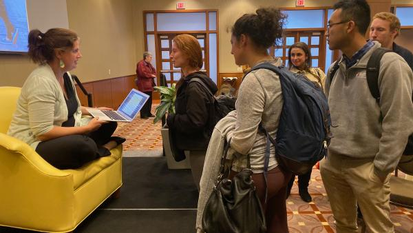 Photograph of Becca Heller speaking with students after the event