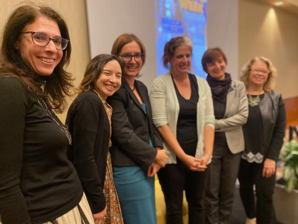 Photograph of Becca Heller with event organizers
